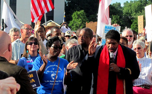 Rev. William Barber, pictured holding microphone, is president of the N.C. NCAA and has been a leader in protests against new voting regulations that some say are hurting minorities.