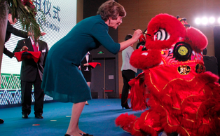 Mary Brown Bullock, executive vice chancellor of DKU, paints a ceremonial lion's eyes at the Kunshan campus's grand opening ceremony in November.