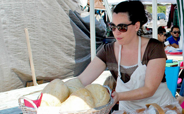 Javiera Caballero, a baker at Durham's Bread Uprising, presents the bakery's products at Green Flea market.
