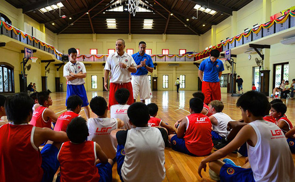 Phil Henderson, in the blue shirt at center, spent the final year of his life in the Philippines opening and running a basketball camp for kids from five to 18 years old. This caption originally said Chris Henderson. The Chronicle regrets the error.