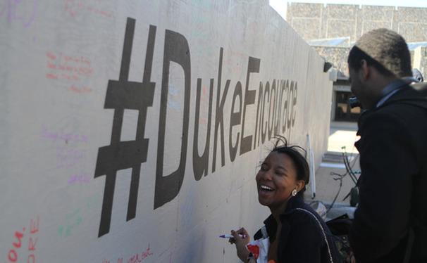 A student writes a supportive phrase on the barrier surrounding the Bryan Center Plaza expansion construction. The Duke Honor Council sponsored the project as part of its campus-wide #DukeEncourage campaign.