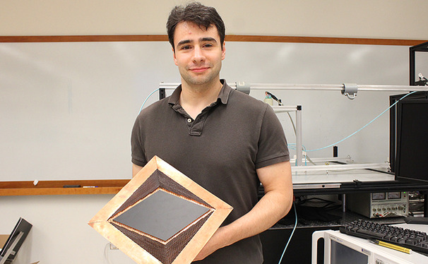 Graduate student Nathan Landy holds an invisibility device, which he worked to develop with engineering professor David Smith.