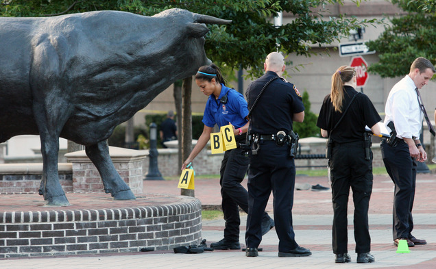A crime scene investigator marks evidence at the site of the shooting.