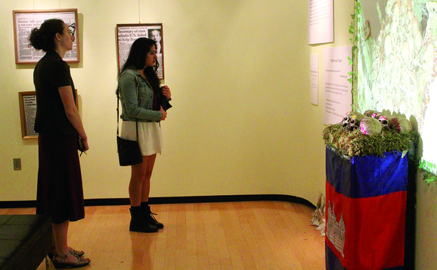 Visitors observe a multimedia exhibit representing photos of moments of genocide throughout the world during Genocide Remembrance Week.